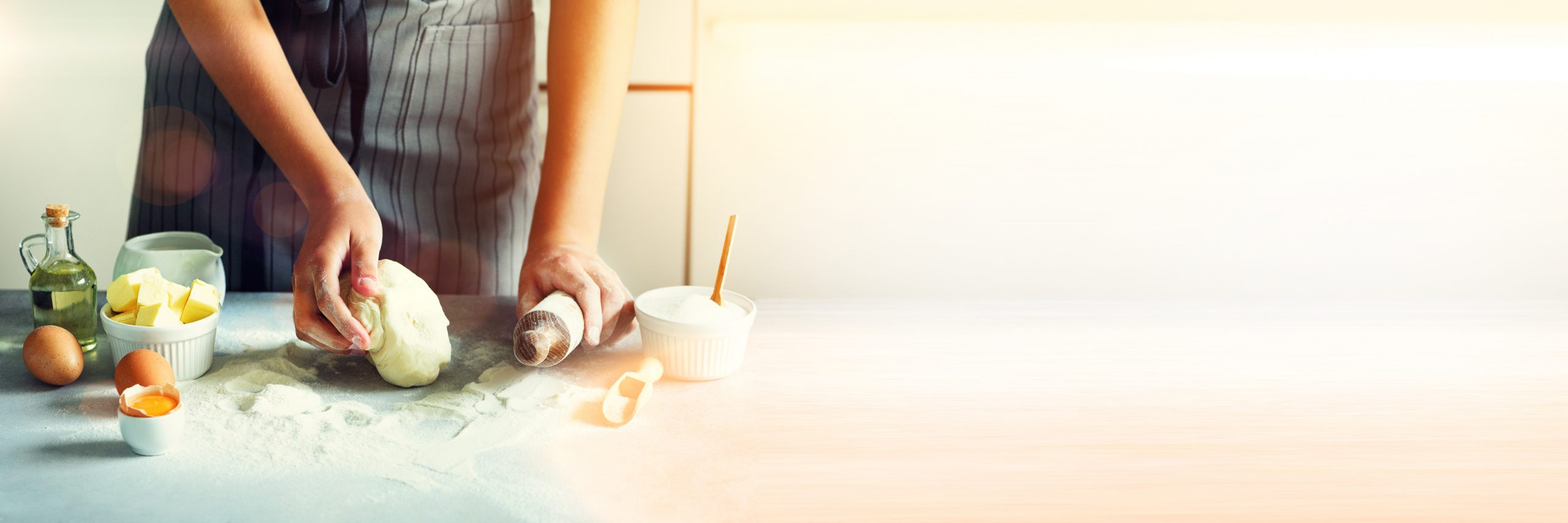 Female hands kneading dough, baking background. Cooking ingredients – eggs, flour, sugar, butter, milk, rolling pin on white style kitchen. Copy space. Banner
